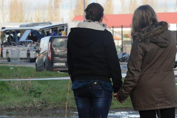 Deux femmes sur les lieux de l'accident du bus scolaire qui a fait 6 morts.