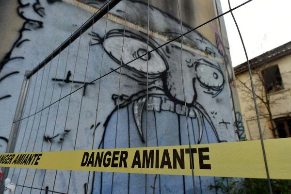 """Un bandeau """"Danger Amiante"""" sur un site en cours de nettoyage."""