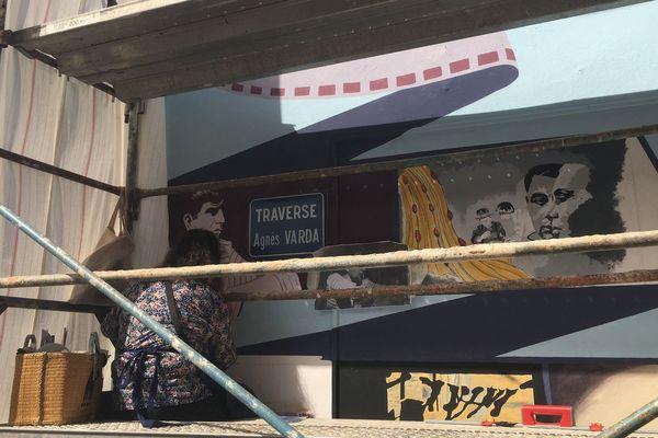 L'artiste américaine Barbara Carrasco peignant une fresque hommage à Agnès Varda à la Pointe Courte à Sète