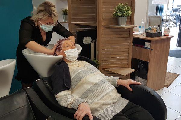 Méloée, assistante coiffeuse, lave les cheveux de Ginette avant sa mise en plis hebdomadaire