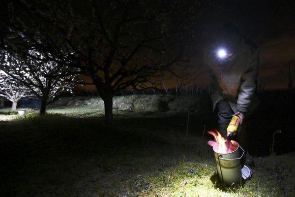 Un arboriculteur utilise une bougie anti-gel pour réchauffer ses cultures.