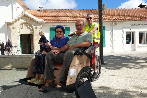 Jean-Louis Klein promène des personnes âgées sur un triporteur, dans Saint-Pierre d'Oléron.