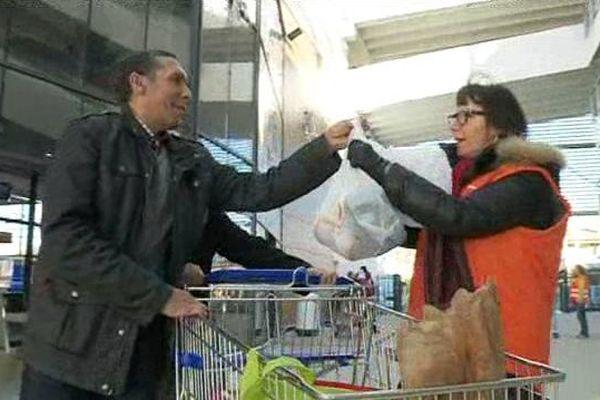 Le client d'un centre commercial donne des aliments non périssables à une bénévole de la banque alimentaire du Gard - 27 novembre 2015