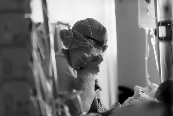 Laura, infirmière, au chevet d'un patient dans le coma. Chaque geste reste d'une infinie tendresse. CHU de Besançon