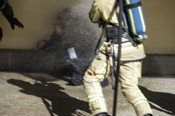 Les pompiers empêchant l'homme de s'immoler devant la Commission européenne.