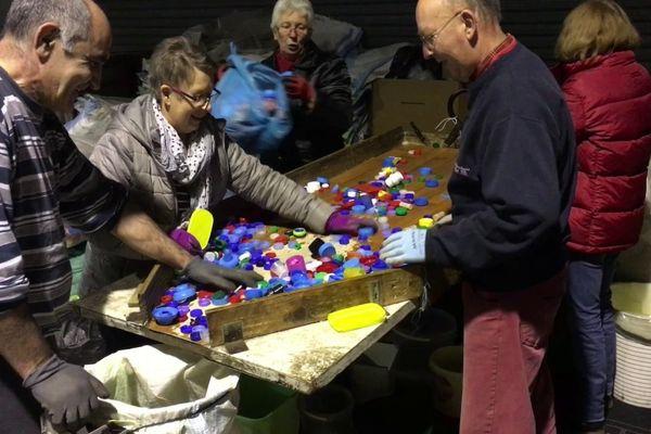 Des bénévoles de l'association Bouchons 276 en action sur une table de tri
