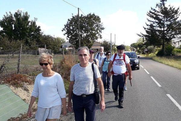 Patrick Maurin, béret sur la tête et bâton de marche,  ce matin accompagnés sur la route par des amis.