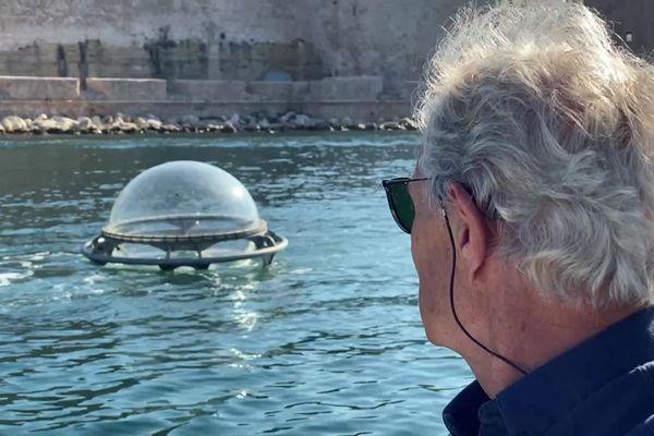 """Jacques Rougerie contemplant son """"Aquabulle"""", quelques minutes avant son immersion."""