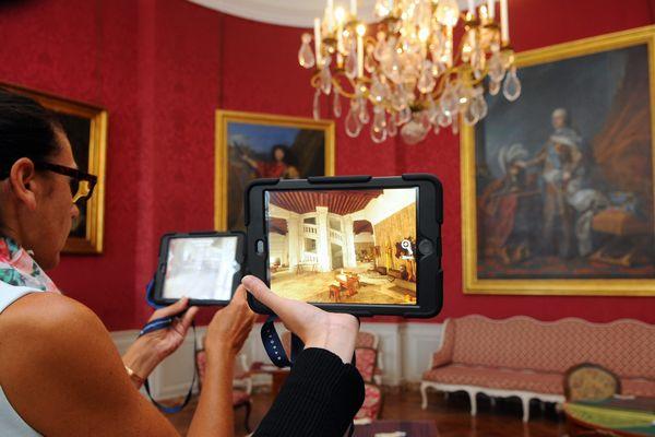 Des touristes découvrent l'envers du décor du château de Chambord avec l'Histopad.
