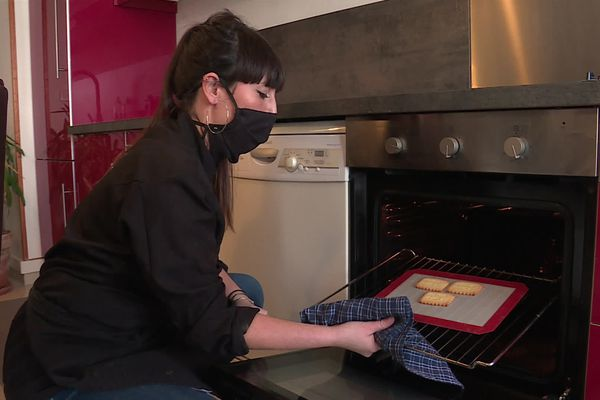Dans sa cuisine, Emilie confectionne des biscuits personnalisés qu'elle vend sur internet.