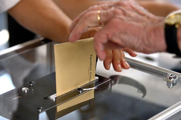 Une électrice dépose un bulletin dans l'urne. Photo d'illustration