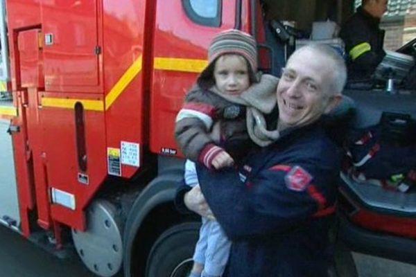 """Noa, 5 ans, dans les bras des pompiers """"ses héros""""."""
