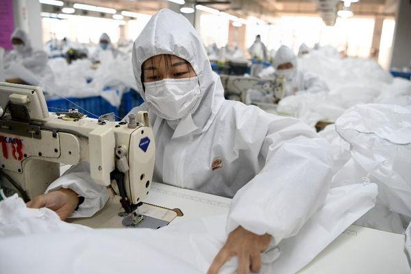Une ouvrière chinoise fabrique du matériel de protection dans une usine.