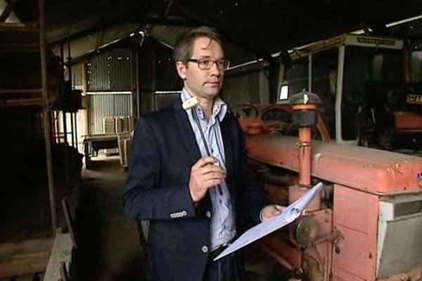 Le commissaire-priseur procède aux enchères d'un tracteur, marteau en main