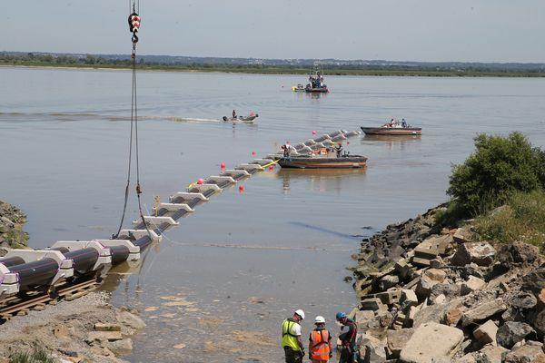 Les fourreaux jumelés descendent sur rail vers la Loire, une fois dans l'eau, les chariots de transports sont retirés par l'homme grenouille puis par la grue.