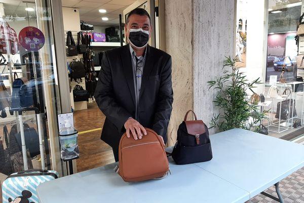 """Marc Jasset, responsable de la maroquinerie Caprice et de l'association des commerçants """"Menton sourire"""", a pu présenter ses articles devant son commerce, malgré le confinement."""