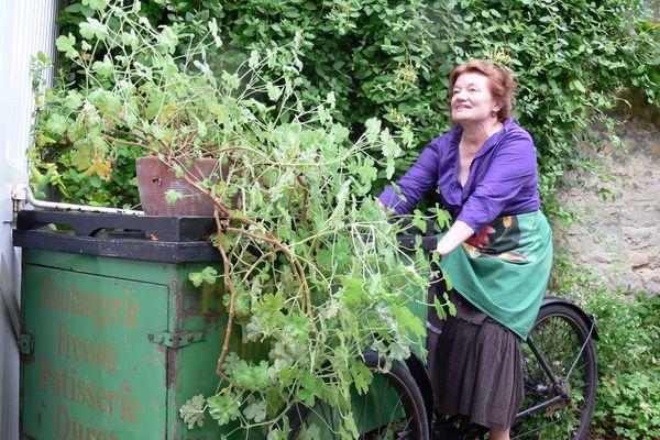 Annie Fresson sur le triporteur installé dans le petit jardin de L'Artisanie... souvenir d'un passé familial omniprésent.