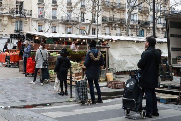 Marché parisien le 21 mars 2020 où les clients se tiennent à un mètre de distance en raison de l'épidémie de Coronavirus.
