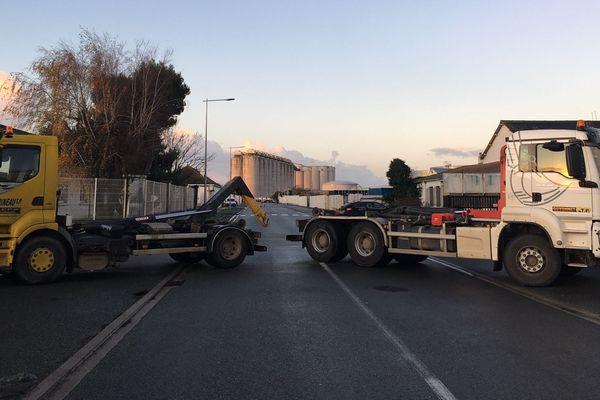 Des bennes et des camions bloquent de part et d'autres l'avenue Bettencourt de la zone industrielle de La Pallice, où sont situés les dépôts pétroliers