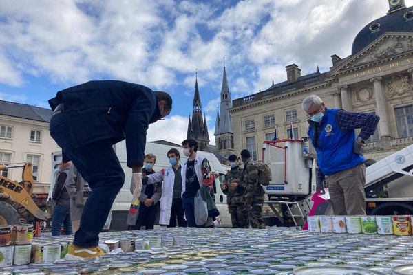 Les élèves de l'école des Métiers d'Art de Châlons aidés par les militaires du service militaire volontaire montent boîte après boîte la pyramide.