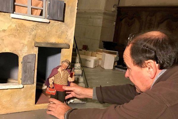 Sur la photo le scénographe présente l'un des santons de Provence habillé avec un tissu très ancien.