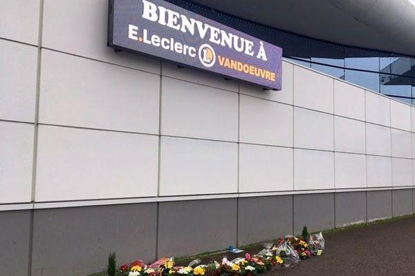Lundi matin, plusieurs fleurs ont été disposées le long du mur de l'entrée du magasin Leclerc de Vandoeuvre-les-Nancy.