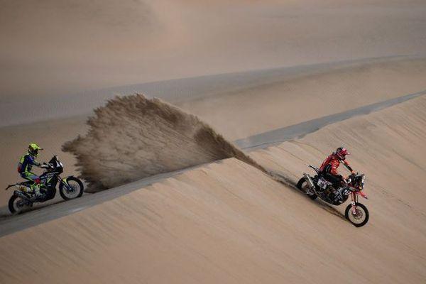 Le motard gardois Michael Metge (à gauche) talonne un pilote bolivien pendant la 9ème étape du Dakar 2019 près de Pisco, au Pérou, le 16 janvier 2019. Michael Metge a remporté cette avant dernière étape.