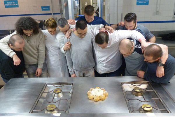 Le chef Philippe Conticini et les détenus de Varennes-le-Grand posent à visages couverts devant leur création, un saint-honoré