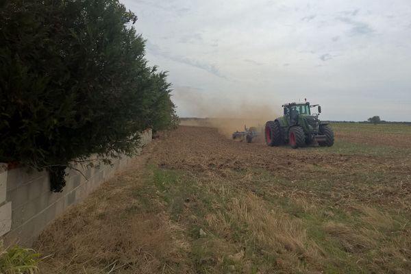 Cet agriculteur laboure sa parcelle, particularité, une maison est enclavée sur ce terrain.