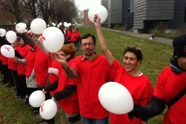 Une cinquantaine de personnes ont formé un ruban rouge humain devant le Nouvel Hôpital Civil de Strasbourg en début d'après-midi