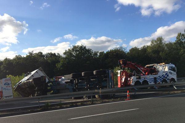 Le camion est couché sur la chaussée avec sa remorque sur l'autoroute A71.