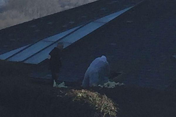 Les enquêteurs sur le toit du musée, analysant l'orifice par lequel se sont introduits les cambrioleurs
