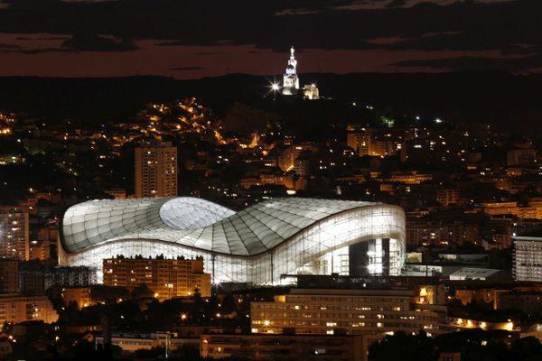 Vue de nuit du nouveau stade Vélodrome ( illuminé ) avec éclairage Au second plan Notre Dame de La Garde.