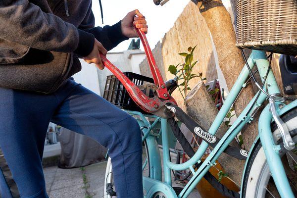 Un homme muni d'une grosse pince coupante tente de couper le cadenas d'un vélo pour le voler.