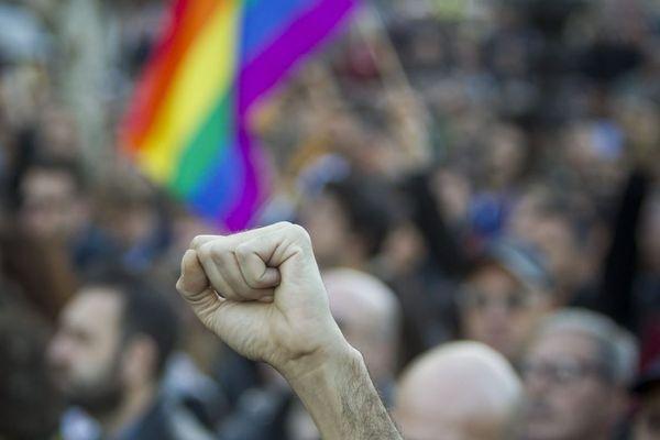 Poing levé devant le drapeau LGBT