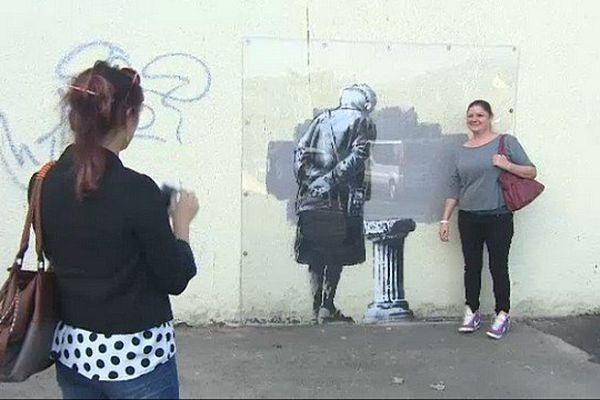 On se presse, à Folkestone, pour se photographier aux côtés de ce nouveau graffiti signé Banksy.
