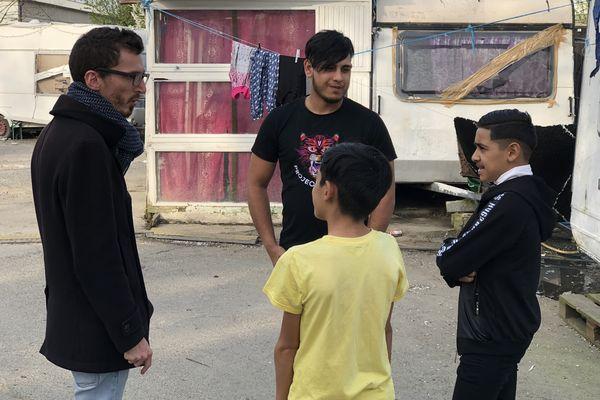 Nathanael Vignaud et Andréi Nicolae discutent avec des jeunes roms du campement.