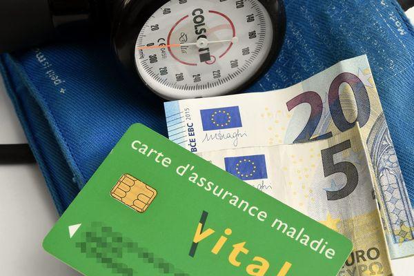 Un tensiomètre, près d'une carte vitale et de billets de banque - Photo d'illustration