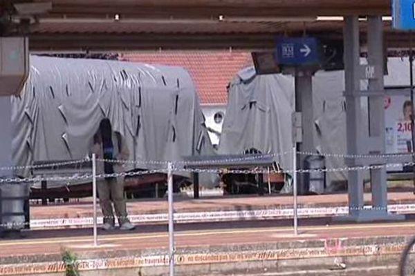 Le 12 août 2013 : des wagons accidentés sont dissimulés sous des bâches grises pour les besoins de l'enquête.