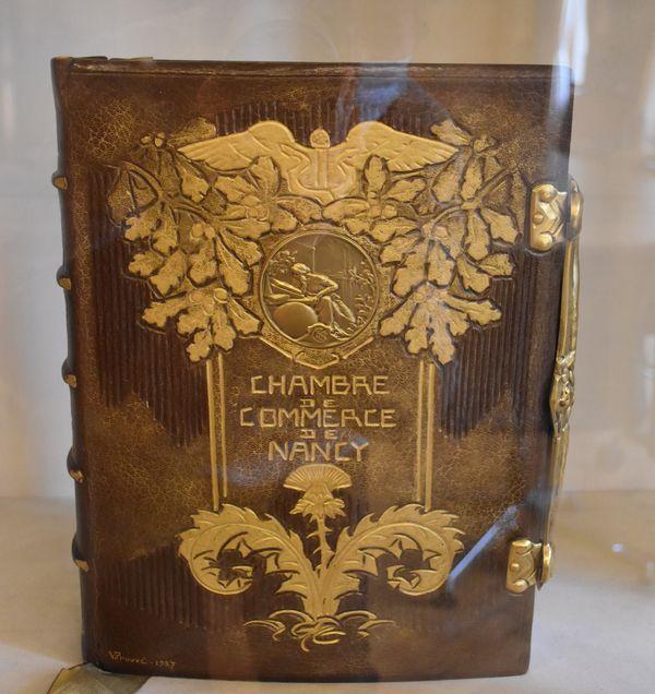 Exposé dans une vitrine de la salle Lyautey, un livre sur la Chambre de commerce de Nancy, dont la couverture en cuir est signée Victor Prouvé.