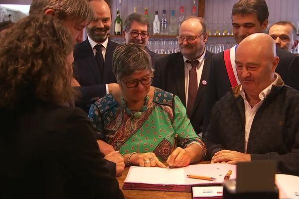Signature du contrat entre les gérants Doudou et son mari Dom et le groupe SOS dans le cadre de l'opération 1.000 cafés à Girancourt (Vosges), jeudi 20 février 2020, sous l'oeil du premier Ministre Edouard Philippe.