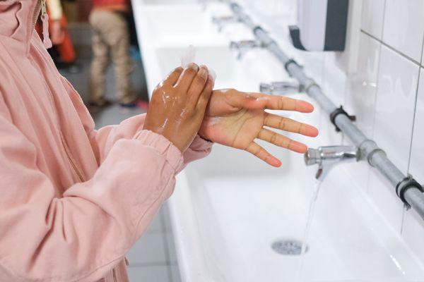 Une petite fille se lave les mains, dans une école de Gagny - Photo d'illustration