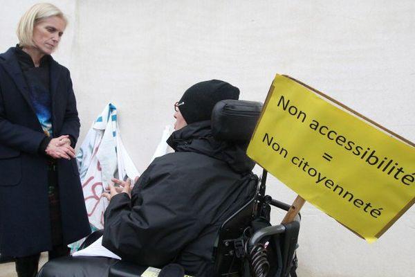 Segolène Neuville, Secretaire d'Etat aux personnes handicapées s'entretient avec un handicapé réclamant une plus grande accessibilité, le 8 décembre 2014.