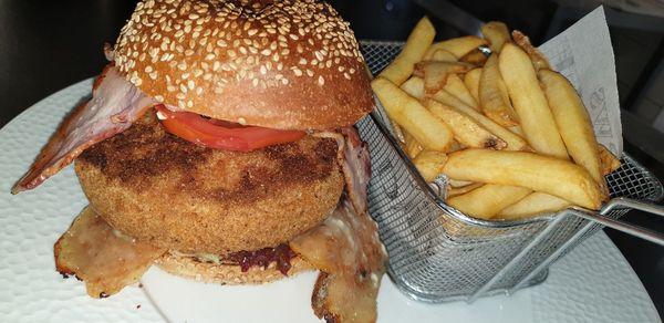 Burger savoyard Bun bio au sésame, sauce burger, salade, tomate, oignons frits, cornichon steak haché charolais, reblochon, galette de pomme de terre, bacon, oignons frits accompagné de frites
