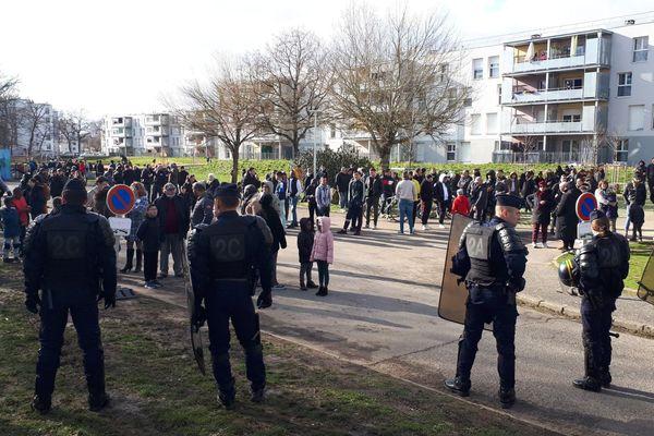 Un cordon de police encadre les habitants, en attente du président Emmanuel Macron, aux abords du gymnase de la Doller
