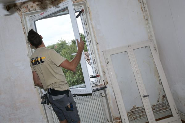 Un artisan remplace les anciennes fenêtres d'une habitation, par des fenêtres double vitrage.