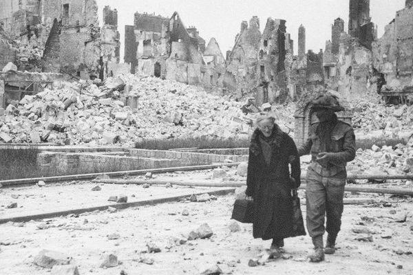 En juin 1944, dans la ville de Caen rasée par les bombardements, un soldat américain accompagne une vieille femme à travers les ruines.