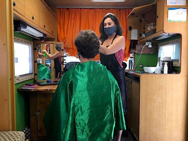 Sonia coiffe Nicolas dans son salon itinérant aménagé dans un camping-car à Fourquevaux près de Toulouse