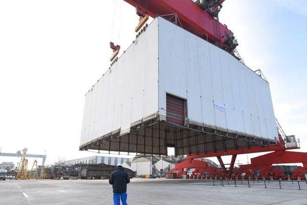 Pour donner la mesure de l'extension, un abri de pré-montage de 40 mètres sur 40 mètres a été déposé sur le sol. La surface de l'extension permet d'en accueillir 6 en même temps.
