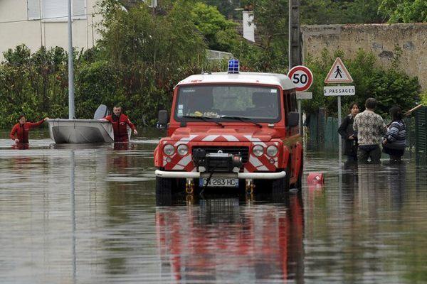 Les pompiers marchent avec leur bateau dans une rue inondée à Montargis, le 1er juin 2016